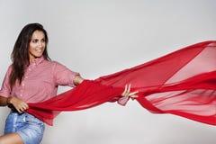 Schönes Frauentanzen mit dem Aufgeben des roten Gewebes Lizenzfreie Stockbilder