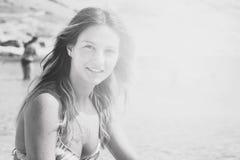 Schönes gebräuntes Mädchen in einem Bikini, der auf einem felsigen Strand sitzt Lizenzfreie Stockbilder