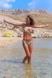 Schönes gebräuntes Mädchen in einem Bikini, der in einem Wasser steht Stockbilder