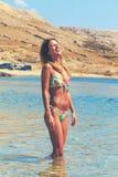 Schönes gebräuntes Mädchen in einem Bikini, der in einem Wasser steht Stockfotografie
