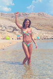 Schönes gebräuntes Mädchen in einem Bikini, der in einem Wasser steht und Hand in einer Luft anhebt Lizenzfreie Stockfotos