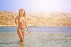 Schönes gebräuntes Mädchen in einem Bikini, der in einem Wasser und in einem Aufgeben steht Stockfotografie