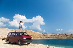 Schönes gebräuntes Mädchen in einem blauen Kleid, das auf einer Dachspitze des roten Packwagens steht Stockfoto