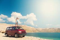 Schönes gebräuntes Mädchen in einem blauen Kleid, das auf einer Dachspitze des roten Packwagens steht und die Sonne untersucht Stockfotografie