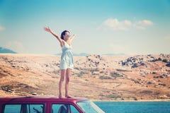 Schönes gebräuntes Mädchen in einem blauen Kleid, das auf einer Dachspitze des roten Packwagens und der ausgebreiteten Arme steht Lizenzfreies Stockbild