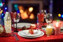 Schönes Gedeck für Feier des Weihnachtsfests oder des neuen Jahres zu Hause Gemütlicher Raum mit einem Kamin und Weihnachtsbaum i stockbild