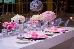Schönes Gedeck mit einer weißen Tischdecke und rosa Servietten Rotes Tischbesteck, schöne speisende Geräte Hochzeits-Dekor-Gewebe stockbilder