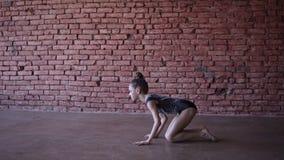Schönes geeignetes Turnermädchen, das gymnastische Übungen im Ziegelsteinentwurfsstudio - Handeln von Spalten, Coupe auf dem Bode stock video footage