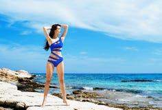 Schönes, geeignetes und sexy Mädchen im blauen Badeanzug, der auf einem Strand am Sommer aufwirft Stockbild