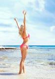 Schönes, geeignetes und sexy Mädchen im rosa Badeanzug, der auf einem Strand aufwirft Lizenzfreie Stockbilder