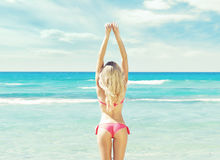 Schönes, geeignetes und sexy Mädchen im rosa Badeanzug, der auf einem Strand aufwirft Lizenzfreie Stockfotos