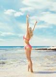 Schönes, geeignetes und sexy Mädchen im rosa Badeanzug, der auf einem Strand aufwirft Stockbilder