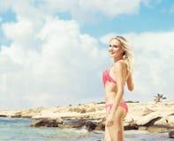 Schönes, geeignetes und sexy Mädchen im rosa Badeanzug, der auf einem Strand aufwirft Stockfoto