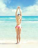 Schönes, geeignetes und sexy Mädchen im rosa Badeanzug, der auf einem Strand aufwirft Stockfotografie