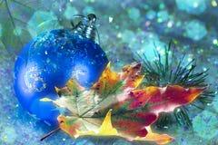 Schönes gelbes rotes grünes Herbstahornblatt nahe einem Ball des neuen Jahres im Schnee mit einem netten unscharfen bokeh und ein Lizenzfreie Stockfotos