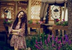 Schönes gelocktes Brunettemädchen auf dem Hintergrund von hölzernem lattic lizenzfreie stockbilder