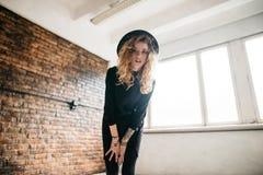 Schönes gelocktes Mädchen in einer Mütze, die gegen eine Backsteinmauer und flüchtige Blicke an der Kamera steht lizenzfreies stockbild