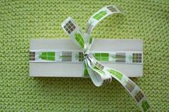 Schönes Geschenk mit einem Band auf einem grünen Hintergrund Stockbilder
