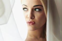 Schönes Gesicht der jungen blonden Braut-Frau. Mädchen-Blick in Window.Bridal-Schleier. Vorhänge Lizenzfreie Stockfotos
