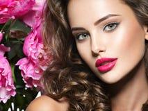 Schönes Gesicht der jungen Frau über den rosa Blumen lizenzfreies stockfoto
