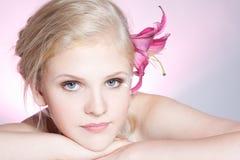 Schönes Gesicht der jungen Frau mit frischer Blume lizenzfreie stockbilder