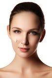 Schönes Gesicht der jungen Frau mit kosmetischer Grundlage auf einer Haut Stockbild