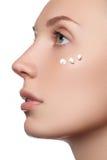 Schönes Gesicht der jungen Frau mit kosmetischer Sahne auf einer Backe Nahaufnahmeportrait getrennt auf Weiß Nahaufnahmeporträt l Stockfoto