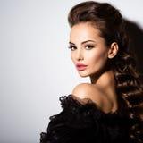 Schönes Gesicht einer jungen Frau im schwarzen Kleid Stockfotos