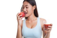 Schönes gesundes asiatisches Mädchen mit Tomatensaft und Apfel Lizenzfreie Stockfotos