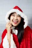 Schönes glückliches asiatisches Mädchen in Santa Claus-Kleidung Stockfoto