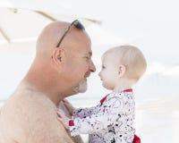 Schönes glückliches ausdrucksvolles blondes Mädchen-Kleinkind auf dem Strand mit ihrem Großvater Lizenzfreies Stockfoto