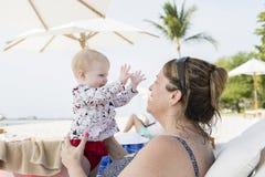 Schönes glückliches ausdrucksvolles blondes Mädchen-Kleinkind auf dem Strand mit ihrer Großmutter Stockfoto