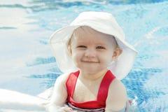 Schönes glückliches ausdrucksvolles blondes Mädchen-Kleinkind mit Sonnenschutz in einem Pool Lizenzfreies Stockfoto
