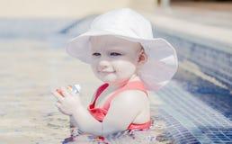 Schönes glückliches ausdrucksvolles blondes Mädchen-Kleinkind mit Sonnenschutz in einem Pool Stockfotografie