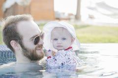 Schönes glückliches ausdrucksvolles blondes Mädchen-Kleinkind mit Sonnenschutz in einem Pool Stockbild