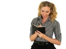 Schönes, glückliches Frauen-Schreiben auf dem Notizbuch-Lächeln Lizenzfreie Stockfotos