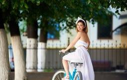 Schönes glückliches Frauenreitfahrrad in der Stadt stockfotos