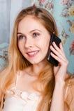 Schönes glückliches junges blondes Mädchen, das auf der Couch spricht O sitzt Lizenzfreie Stockfotografie