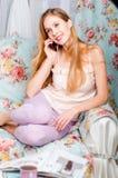 Schönes glückliches junges blondes Mädchen, das auf der Couch spricht O sitzt Lizenzfreies Stockfoto