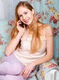 Schönes glückliches junges blondes Mädchen, das auf der Couch spricht O sitzt Stockfoto