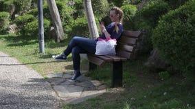 Schönes glückliches junges Mädchen, das den Smartphoneschirm sitzt auf einer Bank im Park im Sommer betrachtet stock footage