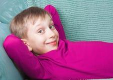 Schönes glückliches Kind, welches die helle purpurrote Strickjacke liegt auf einem Sofa trägt Stockbilder