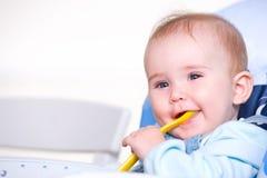 Schönes glückliches Kleinkind mit Löffel Stockbild
