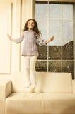 Schönes glückliches Lille-Mädchen, das auf Sofa springt Stockfotografie