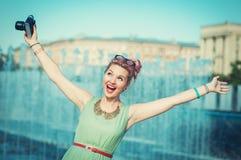 Schönes glückliches Mädchen in der Weinlesekleidung mit Retro- Kamera stockfotografie