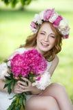 Schönes glückliches Mädchen in einem Kranz und mit einem Blumenstrauß von Pfingstrosen Stockfotografie