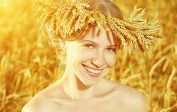 Schönes glückliches Mädchen im Kranz auf dem Weizengebiet im Sommer Lizenzfreies Stockbild