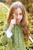 Schönes glückliches Mädchen mit einem Lächeln hält ein gelbes Blatt des Herbstes nahe dem Gesicht lizenzfreie stockfotos