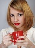 Schönes glückliches Mädchen mit einem roten Cup lizenzfreies stockfoto
