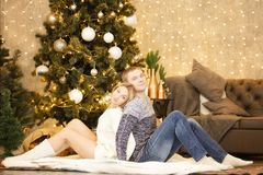 Schönes glückliches Paar, das durch den Weihnachtsbaum sitzt Lizenzfreie Stockbilder